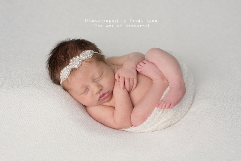 newborn baby girl wrapped in white wrap on simple white background