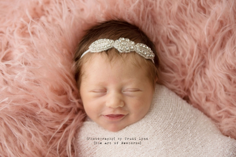 newborn baby girl smiling on pink fur with sparkly headband