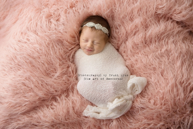 newborn baby girl on pink fur wrapped in white bow smiling