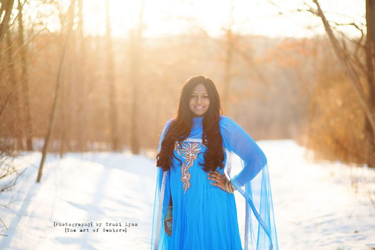 high school senior girl in the winter snow wearing a blue indian gown