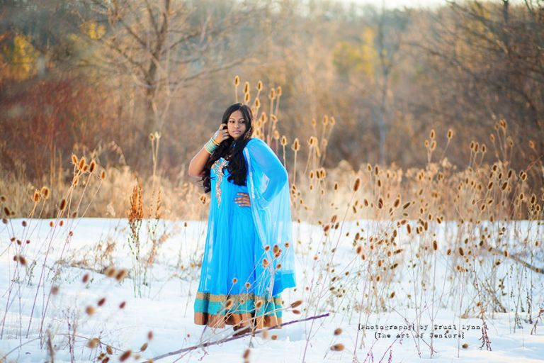 senior girl in the snowy winter landscape wearing a traditional blue indian dress