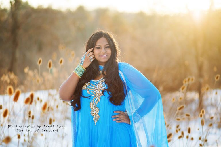 senior girl in blue indian dress in the winter snow at sunset