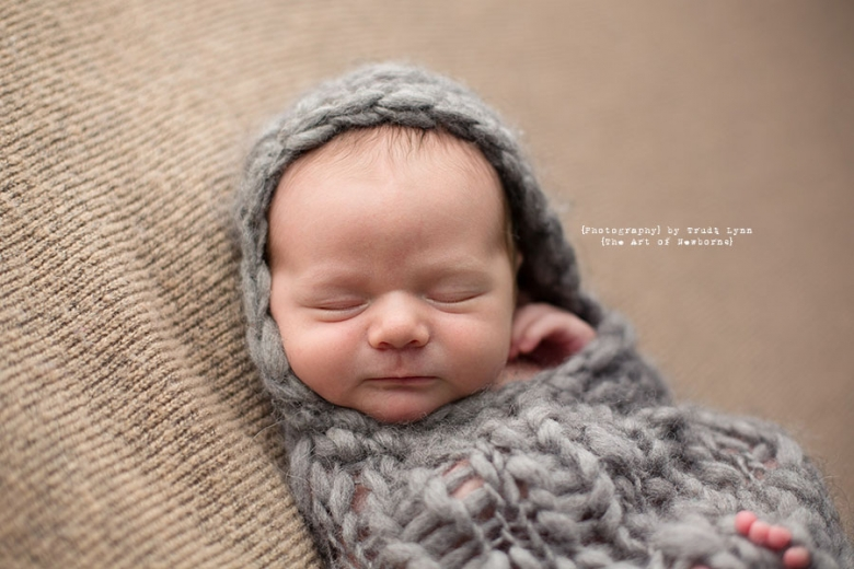 Pinimage newborn baby boy snuggled in gray wrap close up