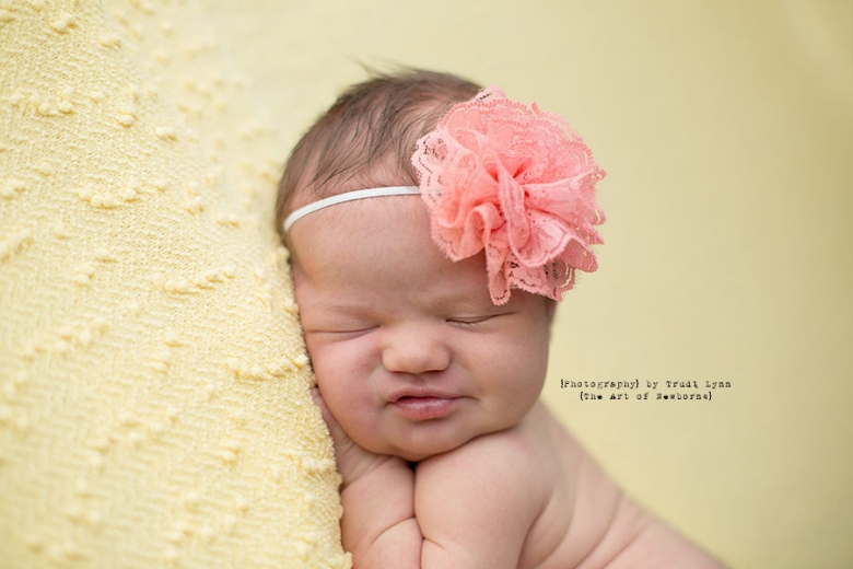 Pinimage newborn baby girl headshot smiling on yellow background