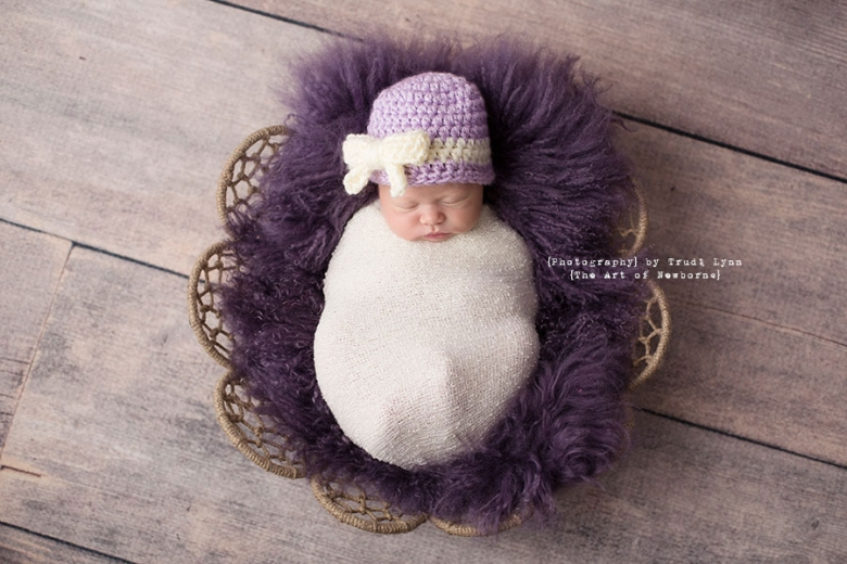 newborn baby girl wrapped in white on purple fur