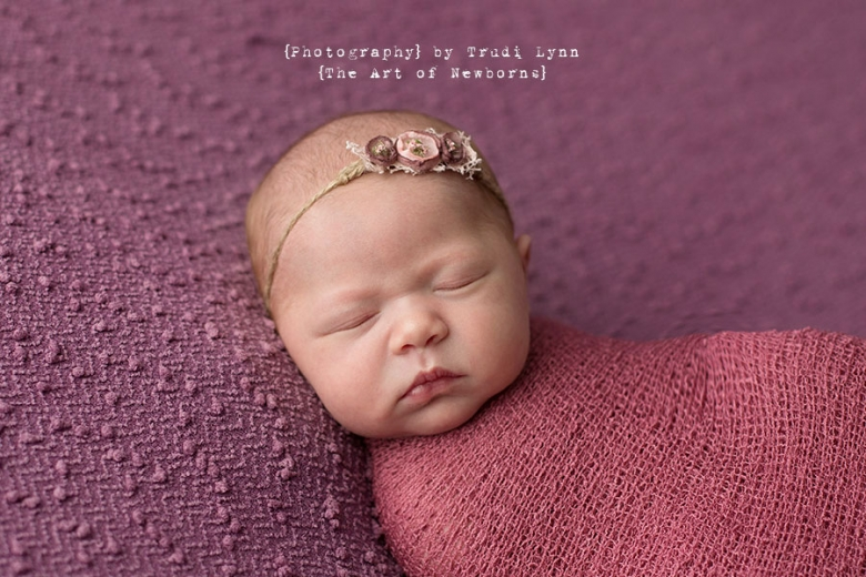 newborn baby girl wrapped in pink wearing vintage tieback