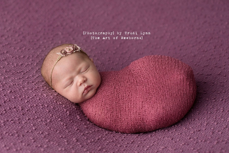newborn baby girl swaddled in dusty rose
