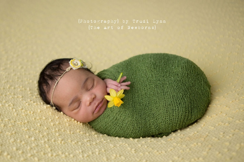 Newborn baby girl swaddled in green wrap holding yellow daffodil