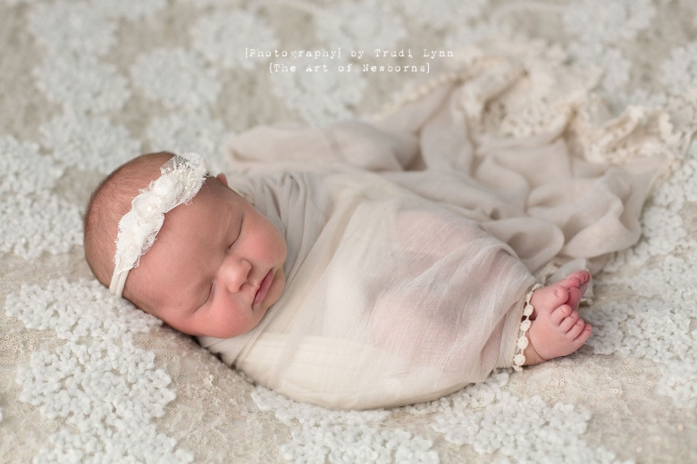 newborn baby girl wrapped in creamy lace wrap with toes peeking out