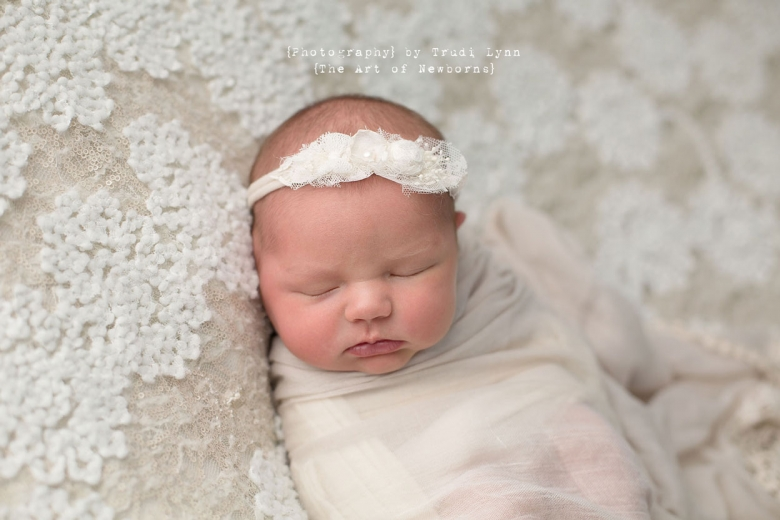 newborn baby girl on creamy white lace background