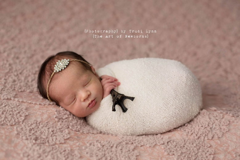 newborn baby girl swaddled in white holding mini eiffel tower statue on pink lace