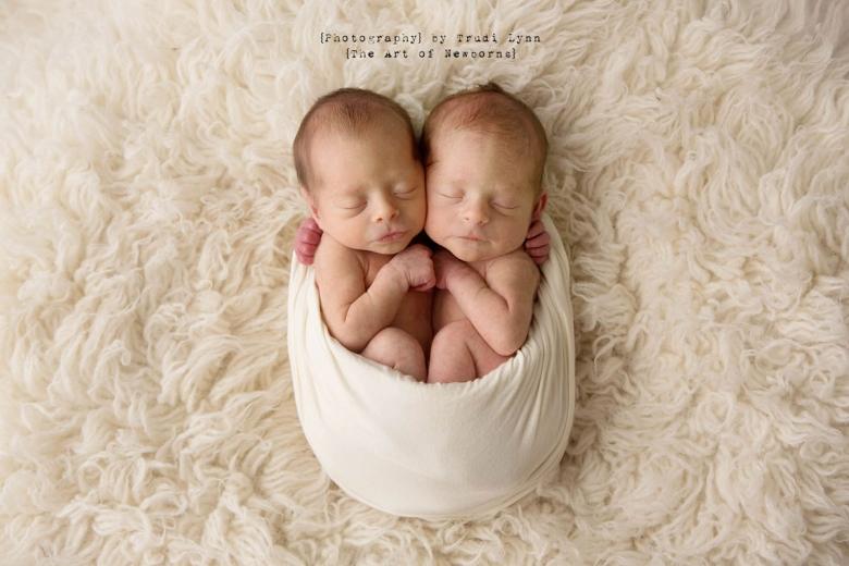 newborn baby girl twins snuggled into egg pose wrap on cream fur