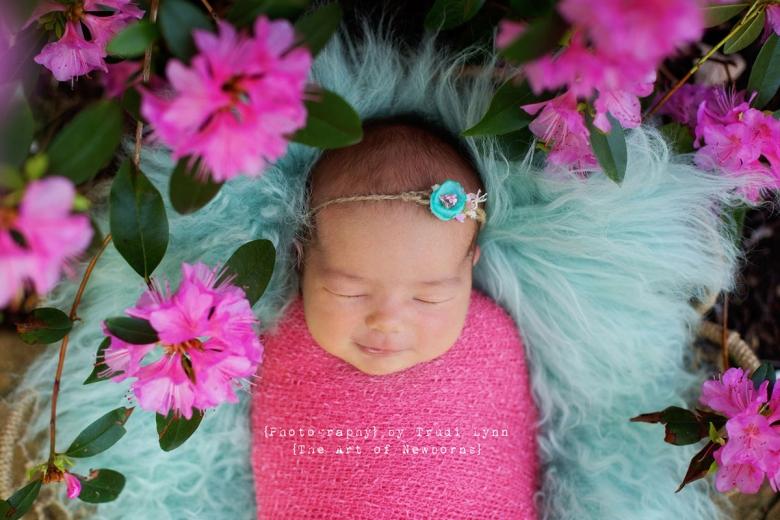 newborn baby girl in outdoor garden with pink azalea flowers